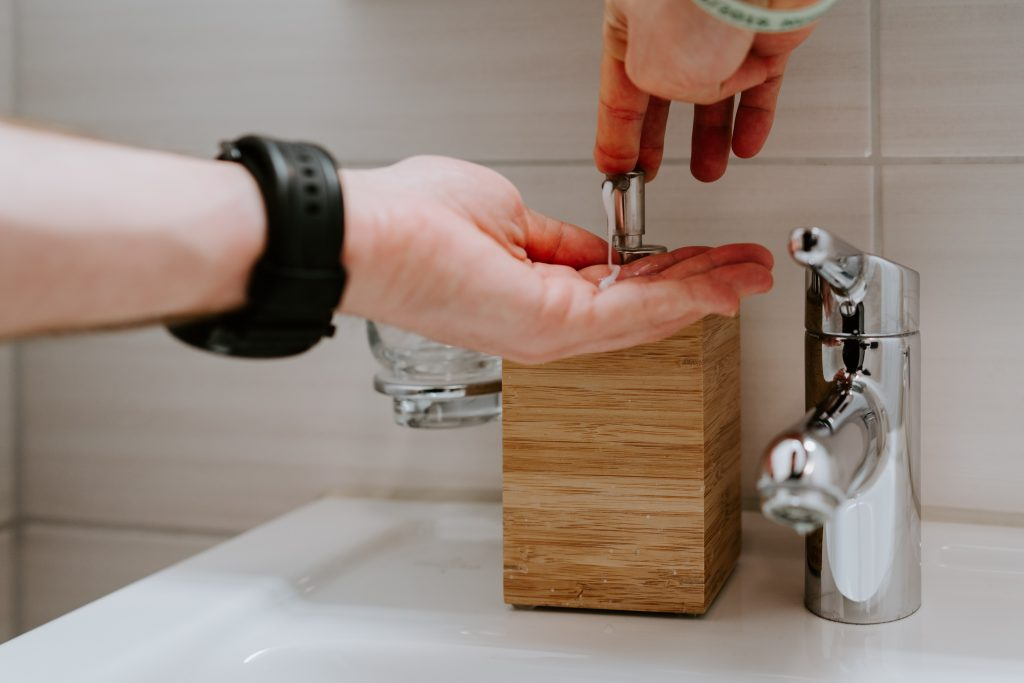 Image of someone using a soap dispenser ready to wash their hands.