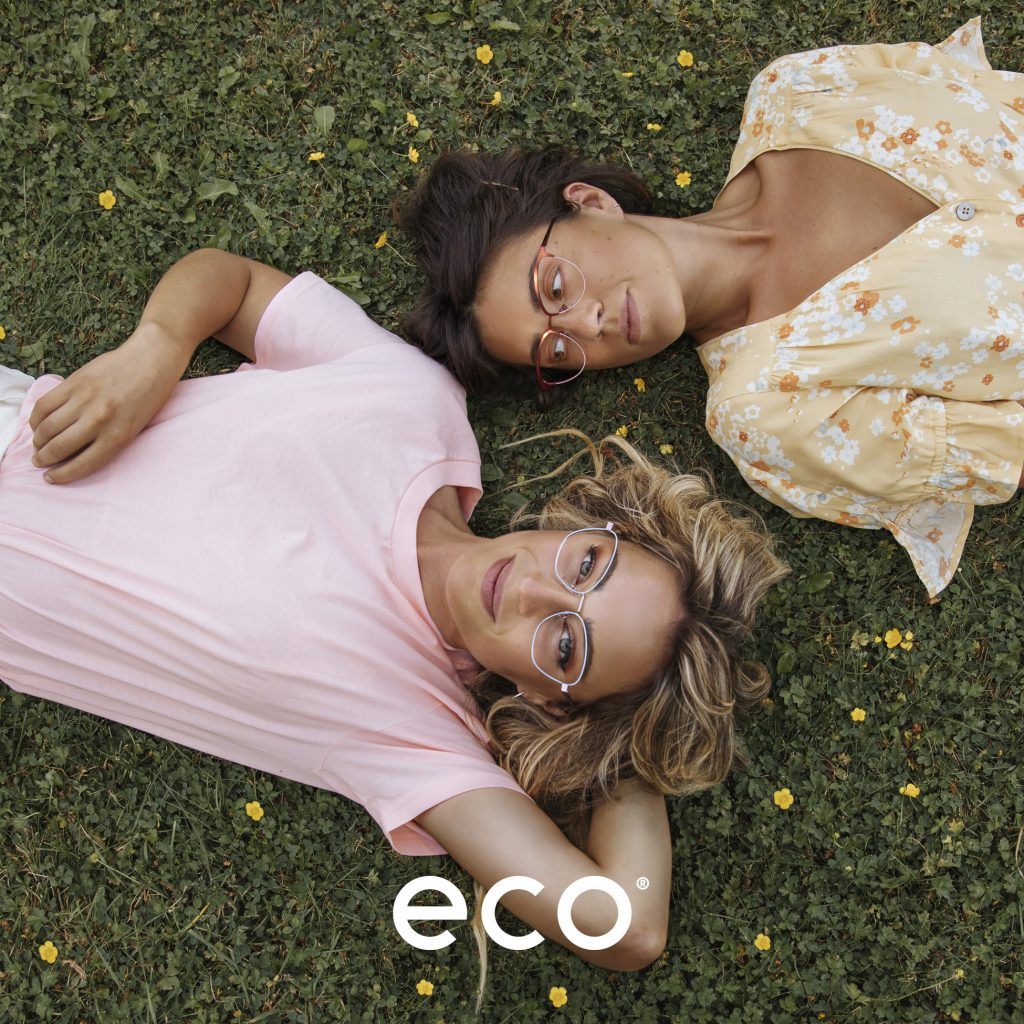 Image of two women lying on the grass wearing Eco eyewear spectacles.